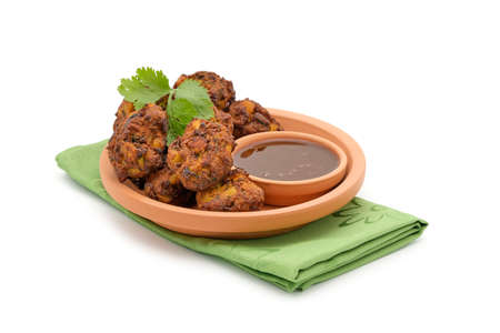 Plate of vegetable pakora a tradtional Indian snack on a white background.
