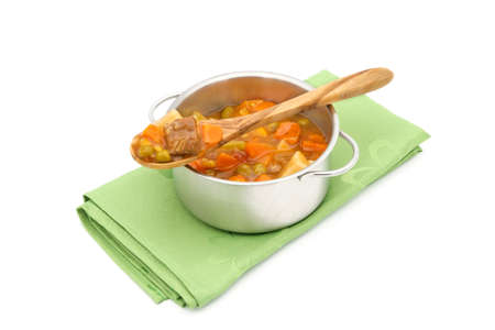 Pot of beef vegetable soup with focus on the contents of the wooden spoon on a white background.