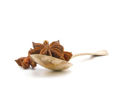 Whole seed pods of star anise in a tarnished vintage antique spoon on a white background with ample copy spave.