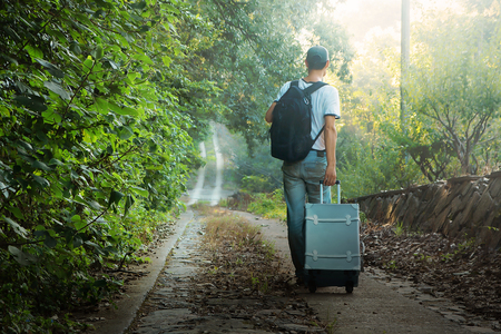A young man carrying luggage on a mountain road