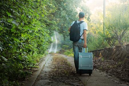 Un jeune homme portant des bagages sur une route de montagne Banque d'images - 84803195