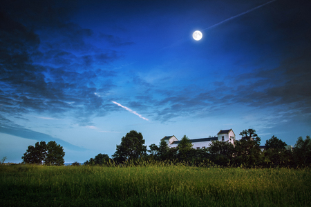 Landscape view of hillside building on meadows under the bright moon
