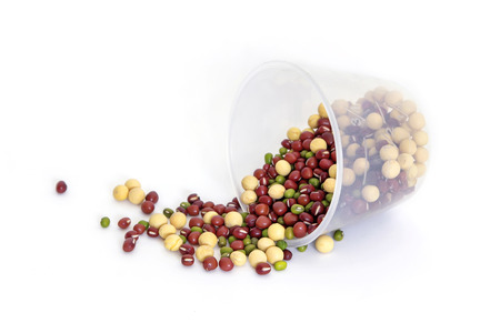 Beans poured from the cup on white background