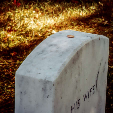 A penny sits on top the grave of a military wife.