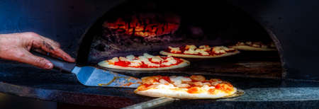 The chef inspecting his pizzas cooking in a wood fired oven at an Italian festival.