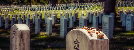 Some Jews believe putting stones on a grave keeps the soul in this world, some believe the stones keep demons from getting into the graves. Stock Photo