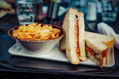 A peanut butter and jelly sandwich made with fresh white bread and served with a side of potato chips.  Oh ya…