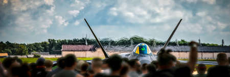 A crowd watches a jet warming up and preparing for take off. Stock Photo