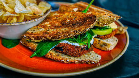 A sandwich made with breaded eggplant, on toast, and served with a side of potato chips. Stock Photo