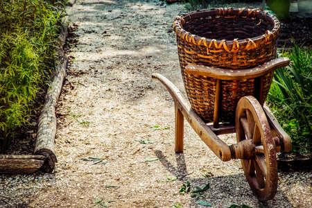 An old wood and wicker wheelbarrow sitting near a garden in Williamsburg, Virginia.