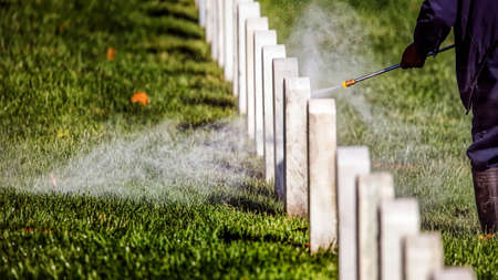 A worker at a national cemetery cleaning headstones with a pressure washer. Stock Photo