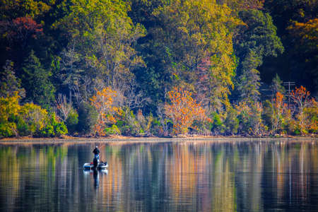 A man fishing by himself on a Virginia waterway with an autumn forest in the background. Stock Photo