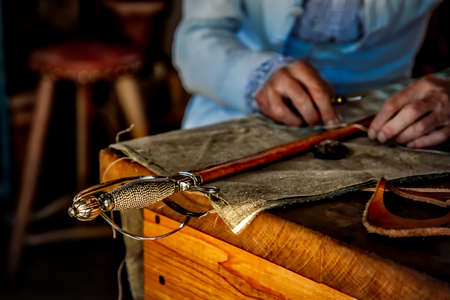 Leather being sewn together on the scabbard of a sword in a Virginia leather shop. Stock Photo