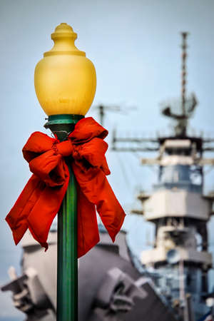 A street lamp decorated for Christmas with a US Navy warship in the background.