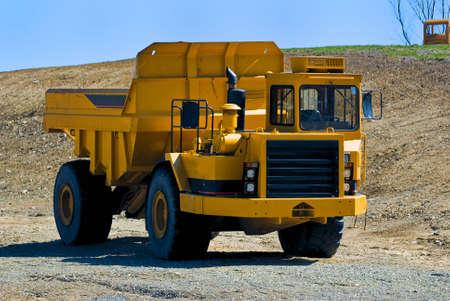 A yellow dump truck parked waiting to be loaded