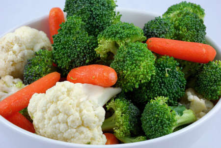 A bowl of mixed vegetables with broccoli cauliflower and carrots Stock Photo
