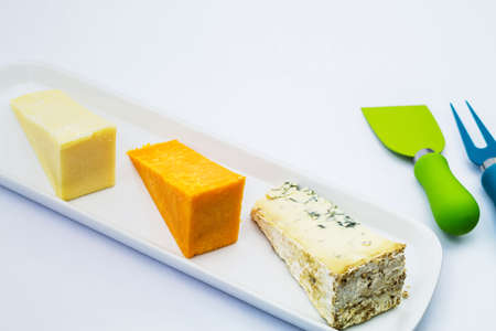 cantal: A selection of cheeses on a board with cheese cutting tools Stock Photo