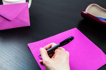 penfriend: Female writing a pen pal letter note at a desk Stock Photo