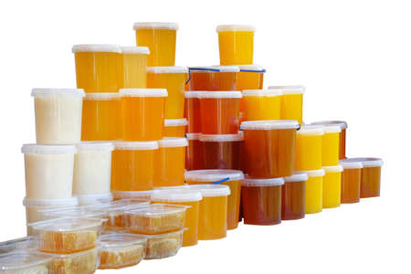 Many plastic containers with fresh honey are on sale at local farmers market. Assortment of different varieties of honey isolated on white background. Imagens - 114180532