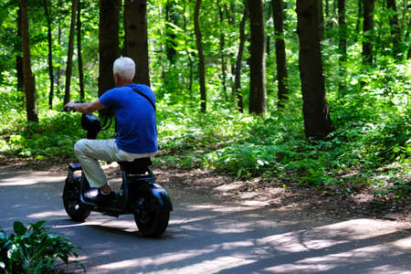 Senior man in blue T-shirt delightedly driving his electric scooter among many green trees.