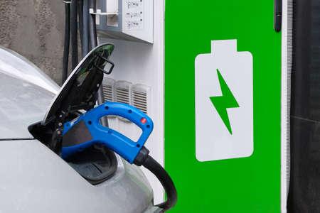 Eco-vriendelijk transportconcept. Auto wordt opgeladen op elektrisch laadstation op parkeerplaats. Detailopname. Stockfoto