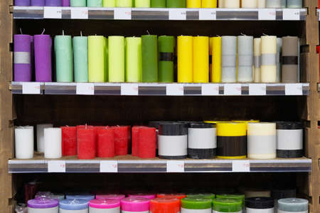 Candles for sale in interior decorating store. Colored variety paraffin candles in cozy candle shop. Discounts on price tags, sale.