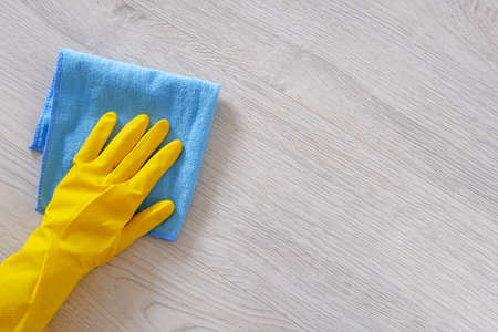 Commercial cleaning company concept. Hand in rubber protective glove with blue microfiber cloth is wiping floor. Copy space.