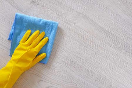 Concepto de empresa de limpieza comercial. La mano en el guante protector de goma con un paño de microfibra azul está limpiando el piso. Copie el espacio.