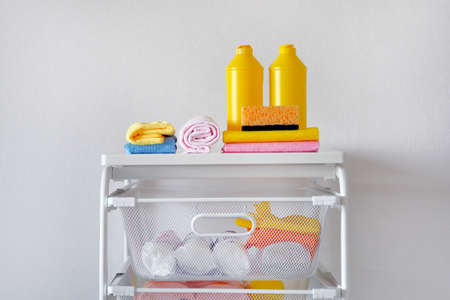 Detergent for cleaning room. Cleaning concept. Yellow plastic bottles with cleaning agent and tools. Regular washing.