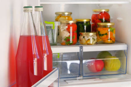 Bottles with homemade red juice and jars of various pickled organic vegetables stand in fridge. Fermented healthy natural food concept. Фото со стока