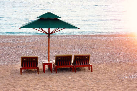 Three beach chairs with green sun umbrella at ocean front. Perfect vacation concept. Coastal landscape. Rest with comfort.