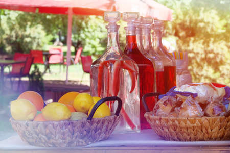 Traditional homemade infused vodka in vintage bottles with fruit and snacks in outdoor cafe. Alcohol drink with red pepper. Summer background and sunlight.
