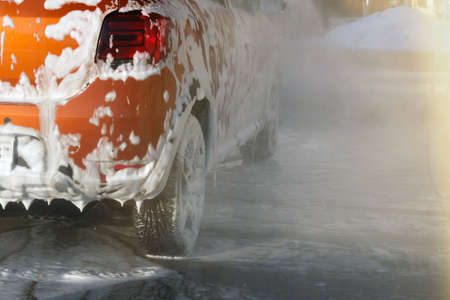 Car is cleaning with soap suds at self-service car wash. White lather on auto. Water splashes around car and soapy water runs down.