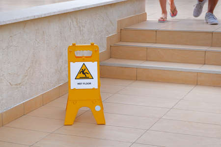 Yellow sign warning about wet floor. Inscription in plate wet floor. Steps on street near hotel.