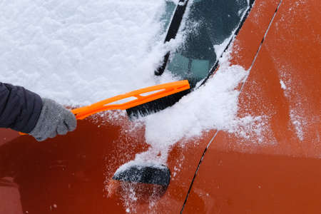 Car covered with snow. Brush in mans hand. Man in gray gloves is brushing orange car from snow. Stock Photo