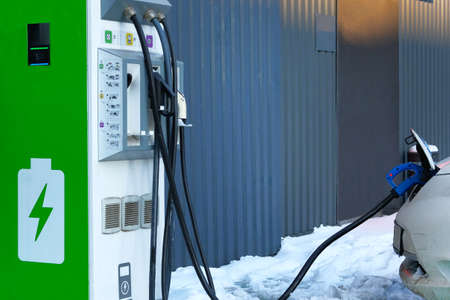 Electric cars charging concept. Car is charged on electric charging station in parking lot. Close up. Stock Photo