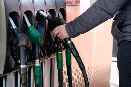 Man fills up his car with a gasoline at gas station. Petrol station pump. To fill car with fuel. Gasoline and oil products.