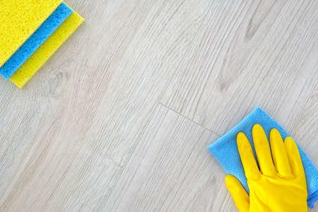 Productos de limpieza laicos planos, copie el espacio. Mano en guante protector de goma amarilla con micro. Concepto de servicio. Vista superior. Foto de archivo