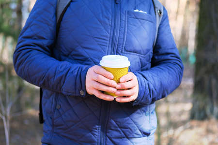 Paper cup for beverages with a takeaway (tea or coffee) in hands on the background of nature with forest. Paper cup in hands of man in blue jacket, social media. Stok Fotoğraf
