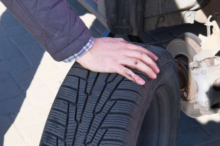 Male hand is changing tyre at car, close up. Wheel balancing or repair and change car tire. Auto repair concept. 免版税图像