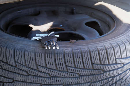 Automobile maintenance concept. Technicians are changing tires. Car service. Changing a flat car tire on road. Close up. Reklamní fotografie