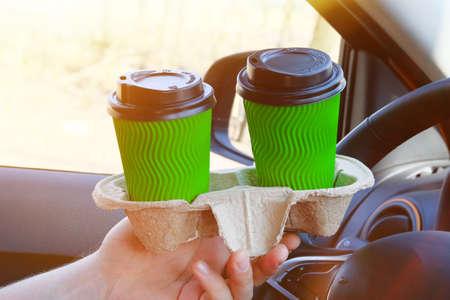 Dos tazas de papel verde con té o café en una mano masculina en coche sobre fondo borroso soleado. Para llevar, redes sociales. Desayuno matutino para pareja en coche.
