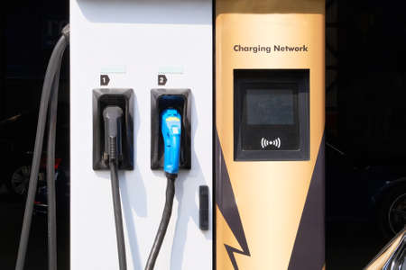 Electric charging station. Car electric charger station installed near iron metal fence near parking lot. Eco friendly transport concept.