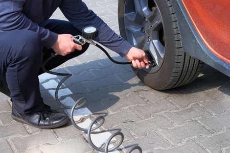 Car service. Man checks pressure in car tires. Hand on auto tire valve. Automobile maintenance concept.