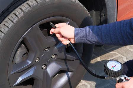 Automobile maintenance concept. Car service. Male hand checks pressure in car tires.