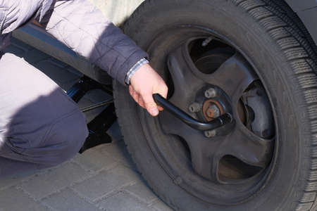 Automobile maintenance concept. Wheel balancing or repair and change car tire. Damaged tyre in car. Reklamní fotografie