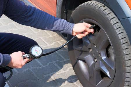 Car service. Man hand checks pressure in vehicle tires. Auto maintenance concept. Reklamní fotografie