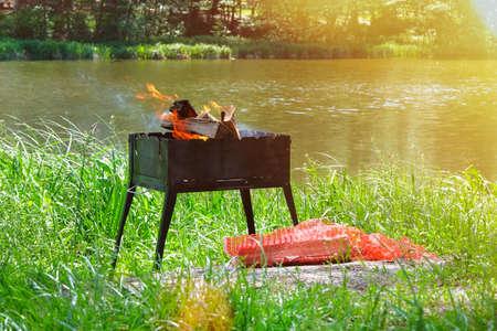 Grill. Picnic. Barbecue on nature. Wood fire prepared for BBQ. Grilling season near water. Sunlight. Archivio Fotografico