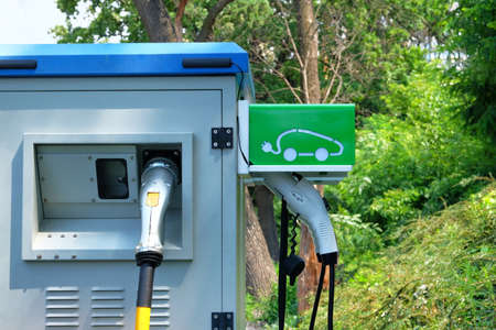 Charger for electric cars in park. Concept of charging electric vehicles. Green icon on electric charging station. . Stock Photo