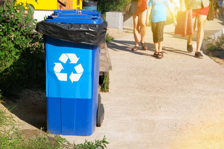 Garbage collection. Waste recycling concept. Blue containers for further processing of garbage. Sunshine.